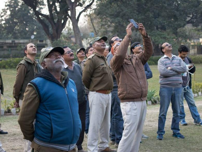 Forest Department staff watching a drone in flight.