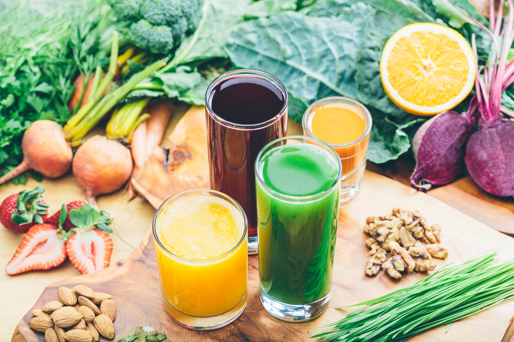 Colorful juices with an assortment of raw ingredients
