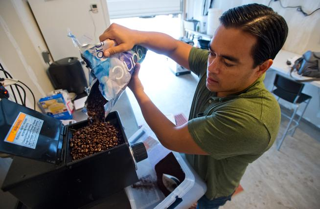 Jason Walsh pours coffee beans into a grinder as he begins to cold brew coffee at his home in Louisville in 2016. Walsh tapped a consultant for help getting his hemp-infused nitro cold brew coffee Native Jack online. (File Photo)