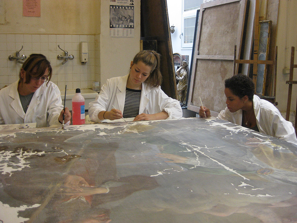 "Photo:  Three students from the first class, left to right: A. Cassidy, M. Philips, C. Clement working on a painting called ""Lo Spirito Santo"" from the 17th century. It belongs to the Pieve (Parish) di Carraia in Prato. The gesso layer has already been applied and the students are now applying a ""background"" layer of gouache."