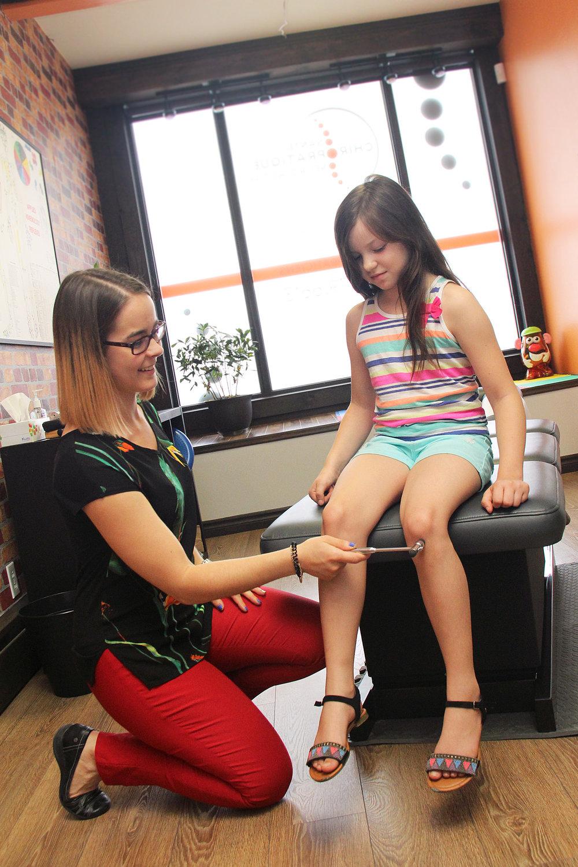 Dre Marie-Eve Bérubé, chiropraticienne, testant les réflèxes ostéo-tendineux sur une jeune patiente