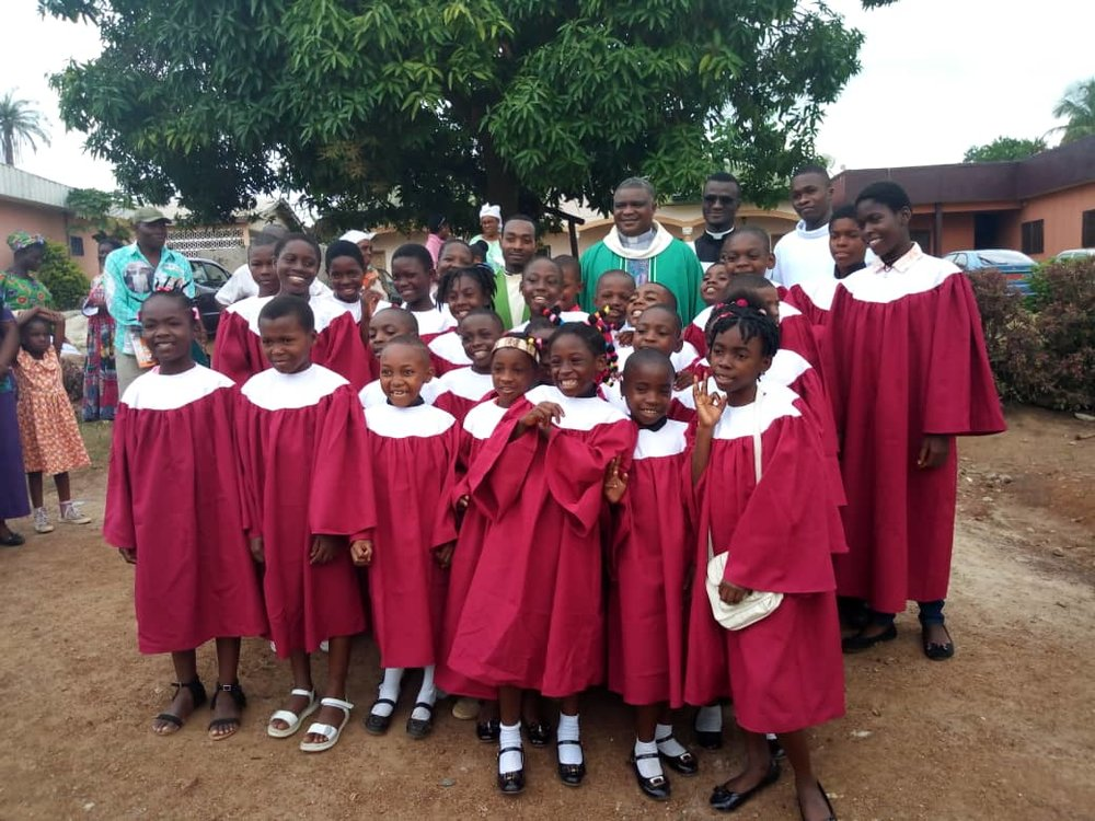 The photo shows Fr.  Bienvenu after Mass at the Cathedral of his diocese together with the children's choir.