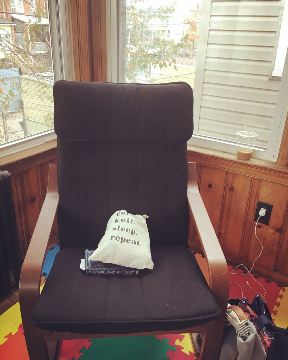 Image: a comfortable chair with a book, knitting and coffee