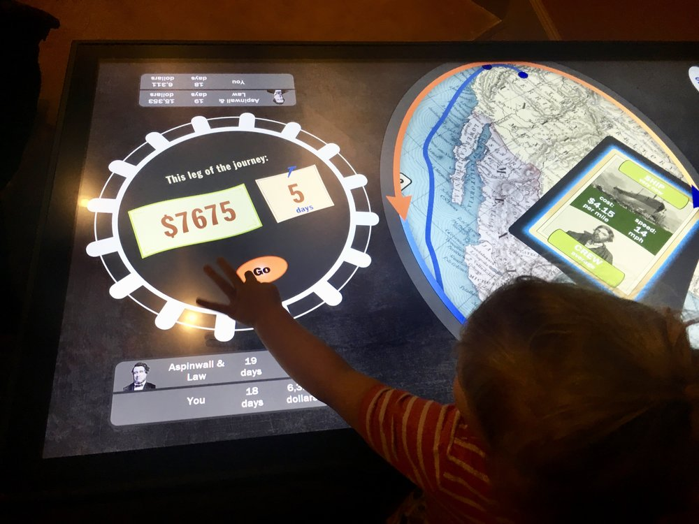 Image: A toddler pressing a button on an interactive exhibit at the US Postal Museum