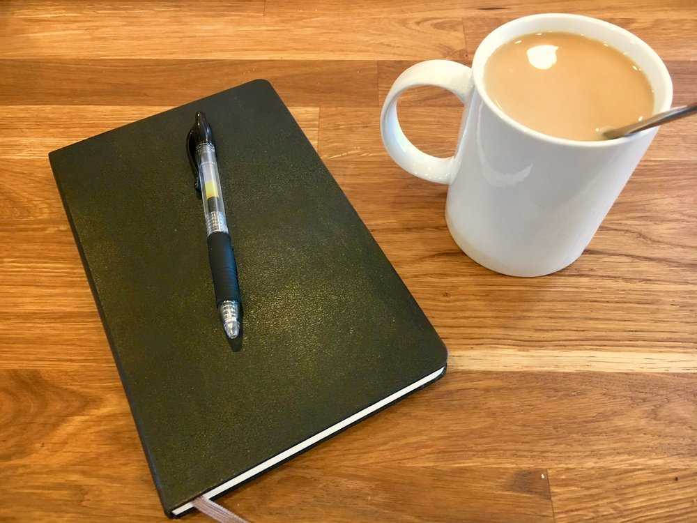 Image: a cup of coffee, notebook and pen on a tabletop