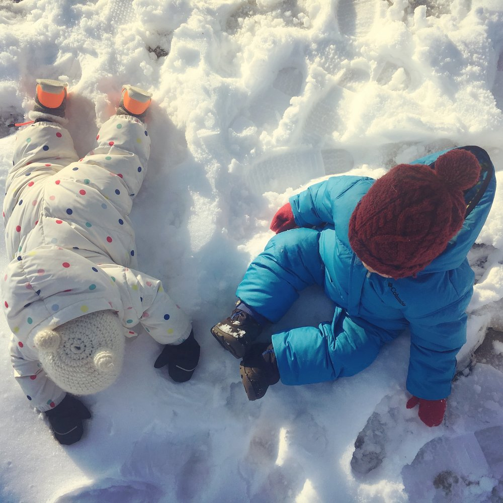 Image: Two babies in snowsuits sitting and crawling in about an inch of fresh snow.