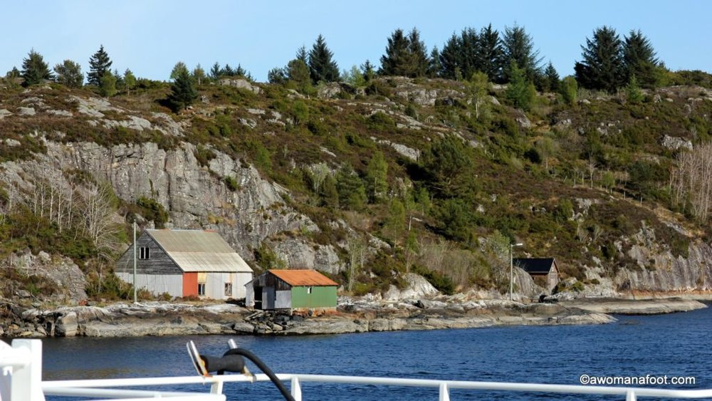 When in Norway you MUST take a ferry ride! Don't miss this fantastic opportunity to see stunning fjords and charming houses perched on rocky shores. Awomanafoot.com | #Norway #fjords #ferry #Scandinavia #VisitNorway #Travel | What to do in Norway | How to see fjords in Norway | Taking a ferry in Norway | Beauty of Scandinavia | Traveling in Scandinavia |