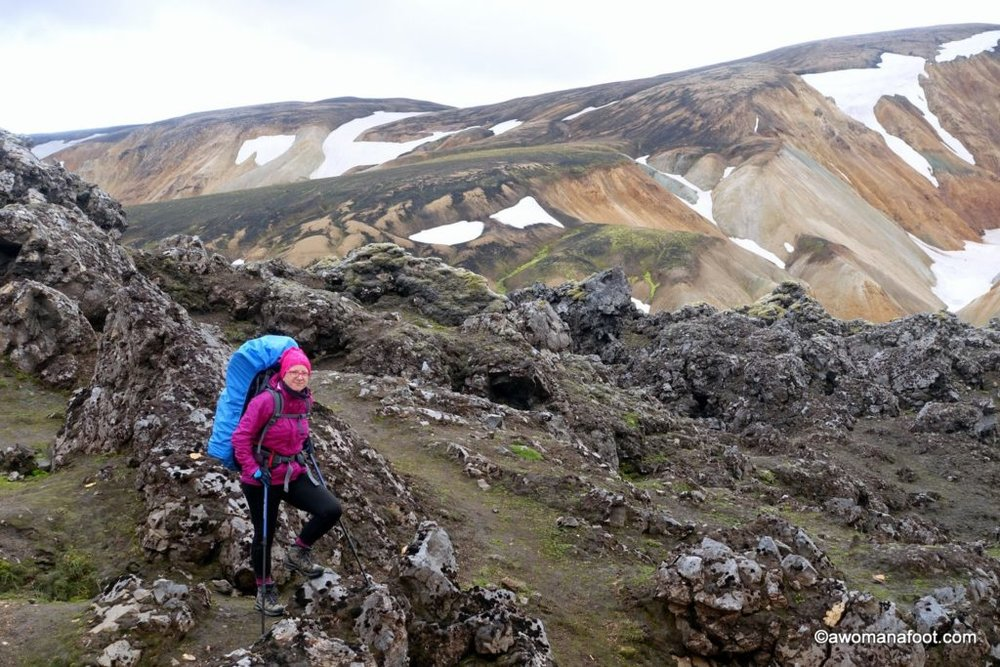 Hiking solo the dramatic Laugavegur trail in Iceland- through black sands, colorful rocks, lava fields, ice bridges, and geysers. Female solo hiking Laugavegur trail | Hiking and camping in Iceland | bucket list trail | geysers | glacier | mountains | Landmannalaugar | Thorsmork | Awomanafoot.com