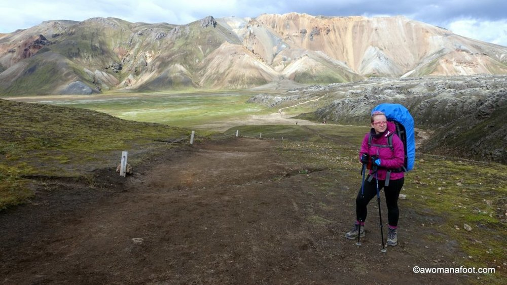 Hiking solo the dramatic Laugavegur trail in Iceland- through black sands, colorful rocks, lava fields, ice bridges, and geysers. Hiking and camping in Iceland | female solo hiking | bucket list trail | geysers | glacier | mountains | Landmannalaugar | Thorsmork | Awomanafoot.com