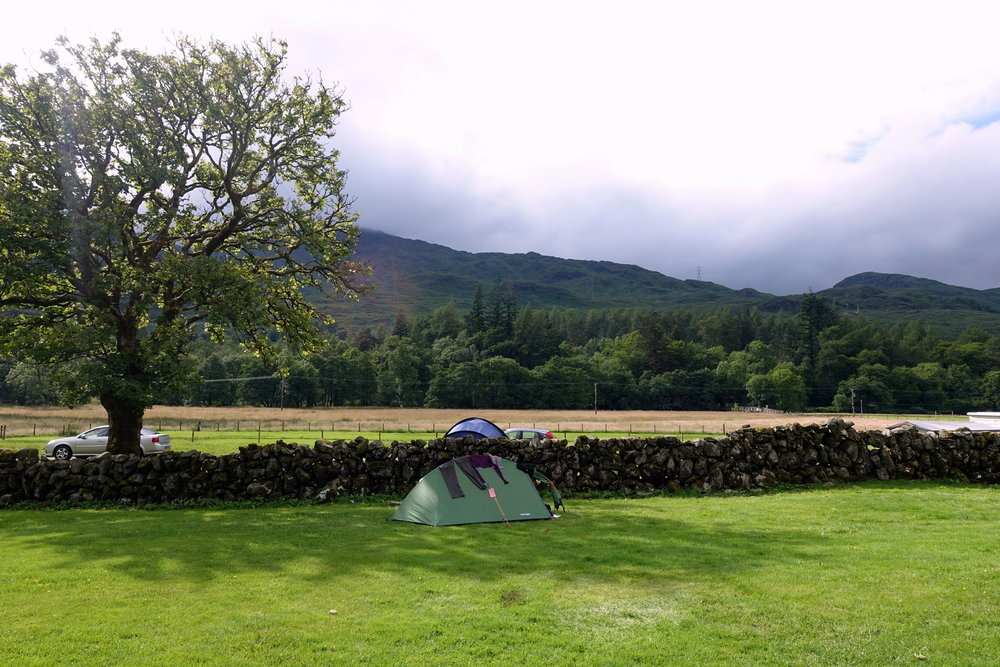 Even on a campsite find a place that offers some wind protection - like this low stone wall.