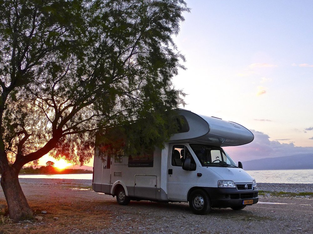 Motorhome parked by a tree on a lakeshore with hills in the background.