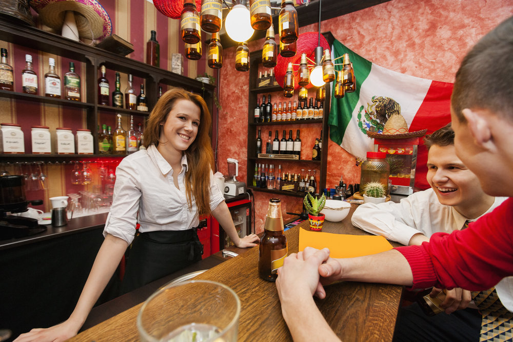 White female bartender with male customers at bar counter with Mexican flag in the background.