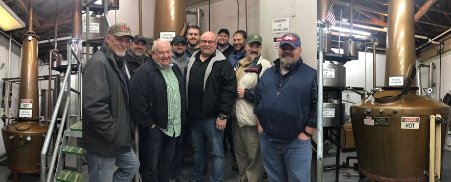 Some of the Administration and   Staff of Whiskey University   are pictured here wedged between the Doubler and the Pot Still at Prichard's Distillery in Kelso, Tennessee. Pictured above from right to left;   Scott Wauford, Troy Rubert, Professor Lt. Colonel Dale Robinson, Professor Lt. Colonel Carl Ingrum, Dakota Mercer, Scott Jackson, Casey Williams, Josh McCrory, Professor Colonel Craig Duncan and Dax Russell.