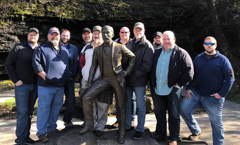 "Some of the Administration and Staff of   Whiskey University   are shown above posing with Jack Daniel in front of the entrance to the  ""Spring at Stillhouse Hollow""  at the Jack Daniel's Distillery. Pictured (from left to right) are;   Casey Williams, Dax Russell, Josh McCrory, Troy Rubert, Professor Colonel Craig Duncan, Master Distiller Jack Daniel, Scott Jackson, Scott Wauford, Professor Lt. Colonel Carl Ingrum, Professor Lt. Colonel Dale Robinson   and   Dakota Mercer."