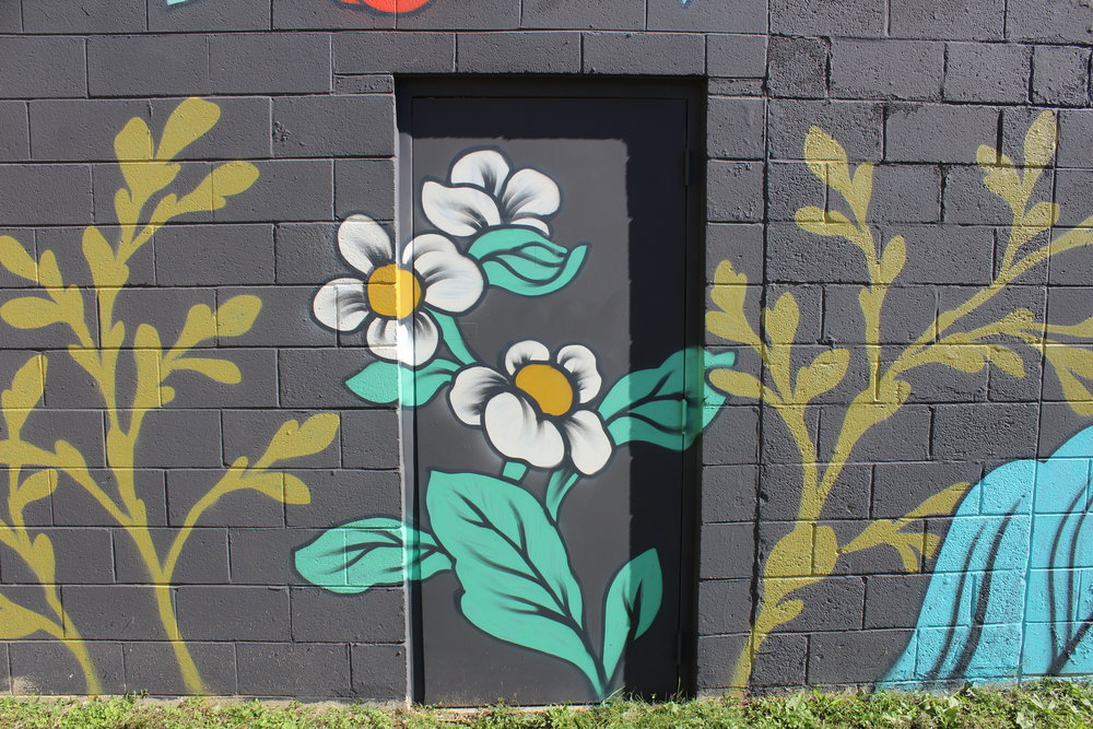 Detail on door of white flowers for Ouizi mural on exterior of Grand Rapids Ballet