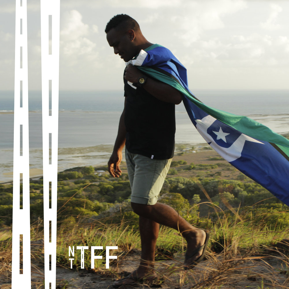 Carry the Flag Danielle Maclean. Thursday Island/Darwin. 28 mins. In 2017 it is the 25th anniversary of the Torres Strait Flag. For Bernard Namok Jnr, Bala B, the flag is a poignant reminder of home, family and the father he hardly knew. Bernard Namok Senior won the flag design competition in 1992 but a year later, at just 31 years, he died leaving behind his wife with four young children. Journey across the Torres Straits with Bala B to honour his fathers legacy. A rich and powerful story of a man whose design created meaning for a people once invisible to mainland Australia, the people of the Torres Strait.