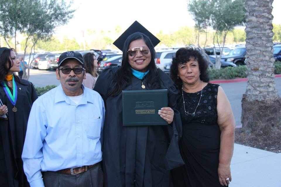 Cassandra with her parents at her Master's graduation.