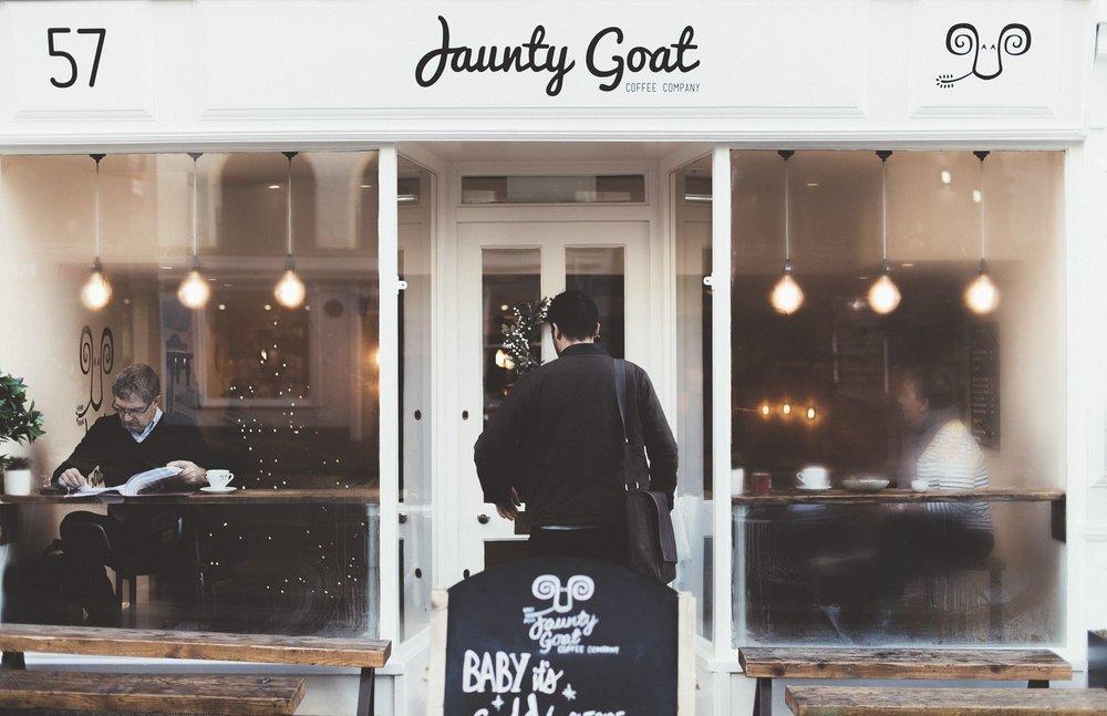 Photo of man entering Jaunty Goat Coffee Shop