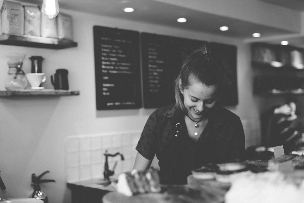 Young female Barista making coffee