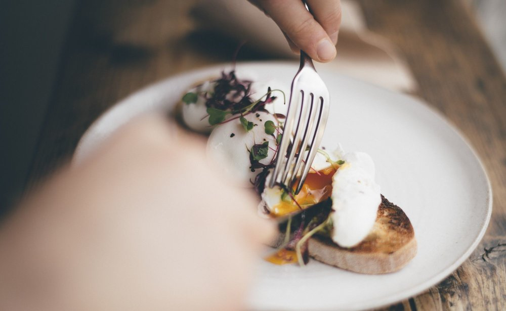 Cutting into perfect poached eggs at Jaunty Goat Coffee