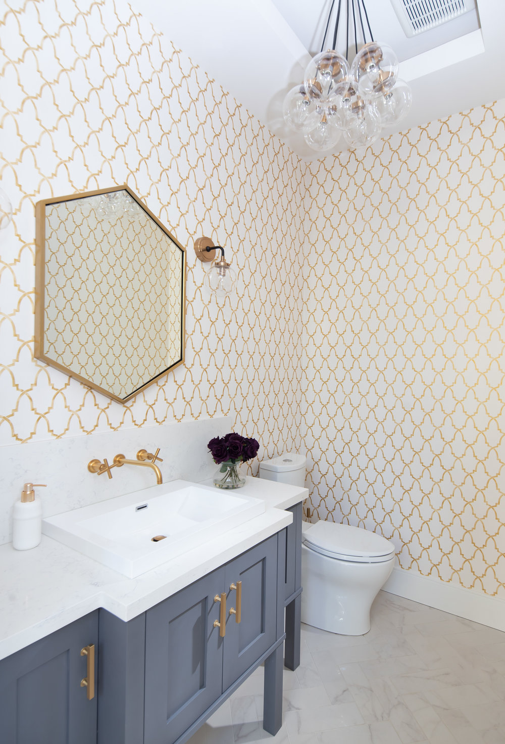 transitional powder room with gold faucet