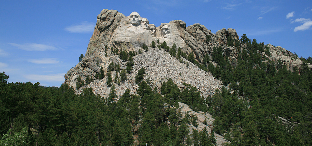 Mount Rushmore from the highway, the moment the road turns to face it directly.