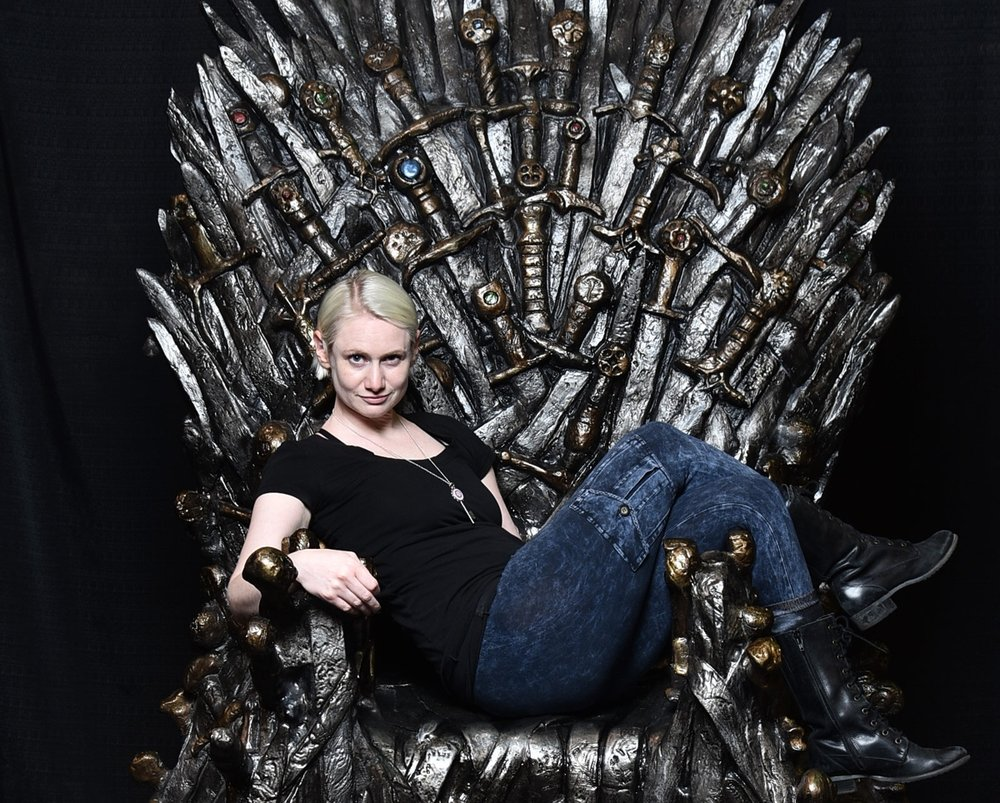 Justine mastin sits on the IRON THONE FROM GAME OF THRONES.