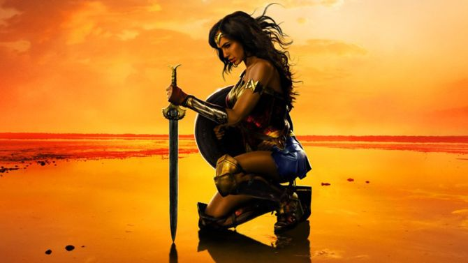Wonder Woman kneels with her sword and shield.