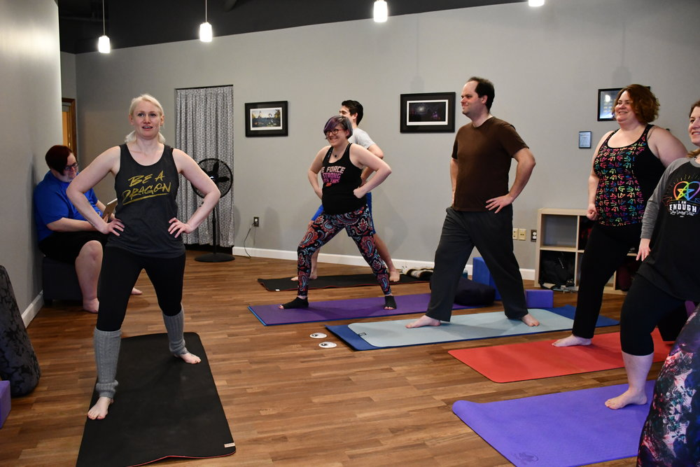 Justine leads yogis at YogaQuest through Warrior 1
