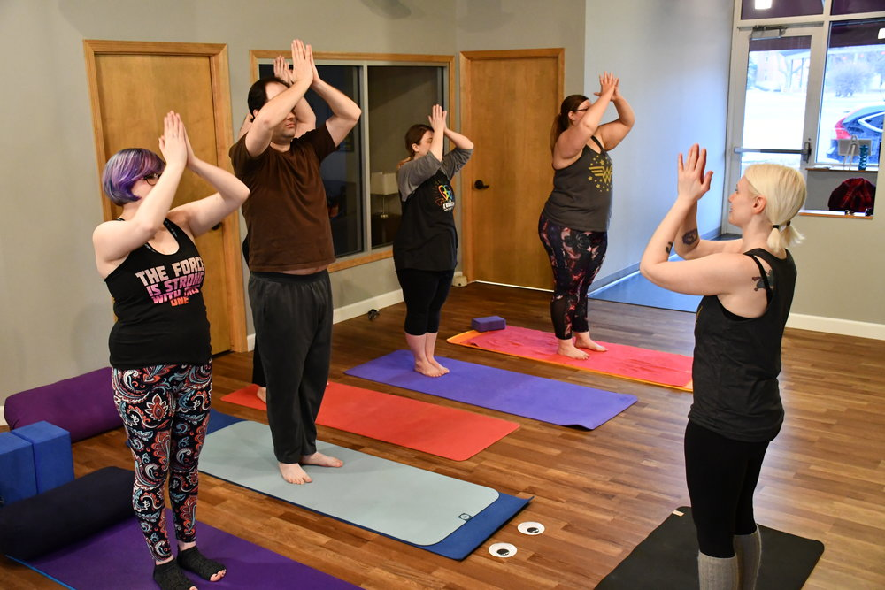 Yogis transition from Upward Salute to Mountain Pose.