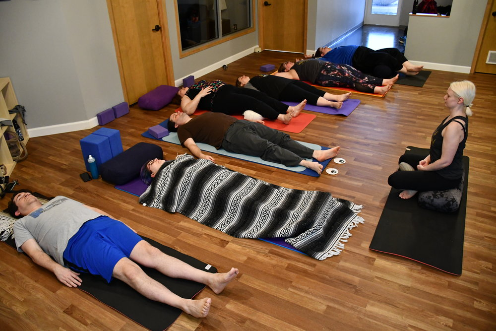 Yogis at YogaQuest enjoy Savasana at the end of class