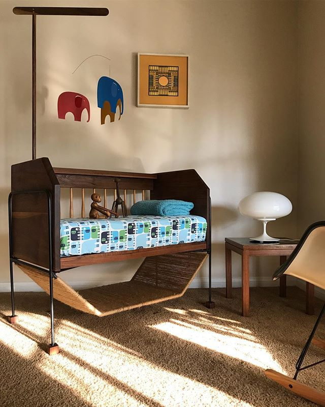 """I designed and built this co-sleeper for my son 4.5 years ago as an extension of our bed and to match the rest of our vintage modern pieces. It's made of solid walnut with hand cut joinery & maple spindles. It sits on an iron frame with a hand woven lower storage shelf in natural jute cord. With my wife and I expecting second 👶🏻 in January I cleaned it up and gave it a few modifications. I lowered the overall height and added walnut end caps for stability, and most importantly made an adjustable attachment for a Flensted """"Elephant Party"""" mobile I picked up from @season.of.change a while back! It's now ready for baby number two! #handmademodern #ironwalnutjute #billcurry #designline #eamesrocker #flensted #elephantparty #danishmobile #zooline #peterpepperproducts #midcentury #midcenturyinspired #midcenturycosleeper #vintagemodern #vintagedesign #handmade"""