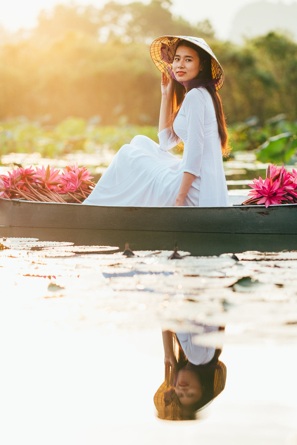 A beautiful sunrise and a vietnamese girl in her tradional white