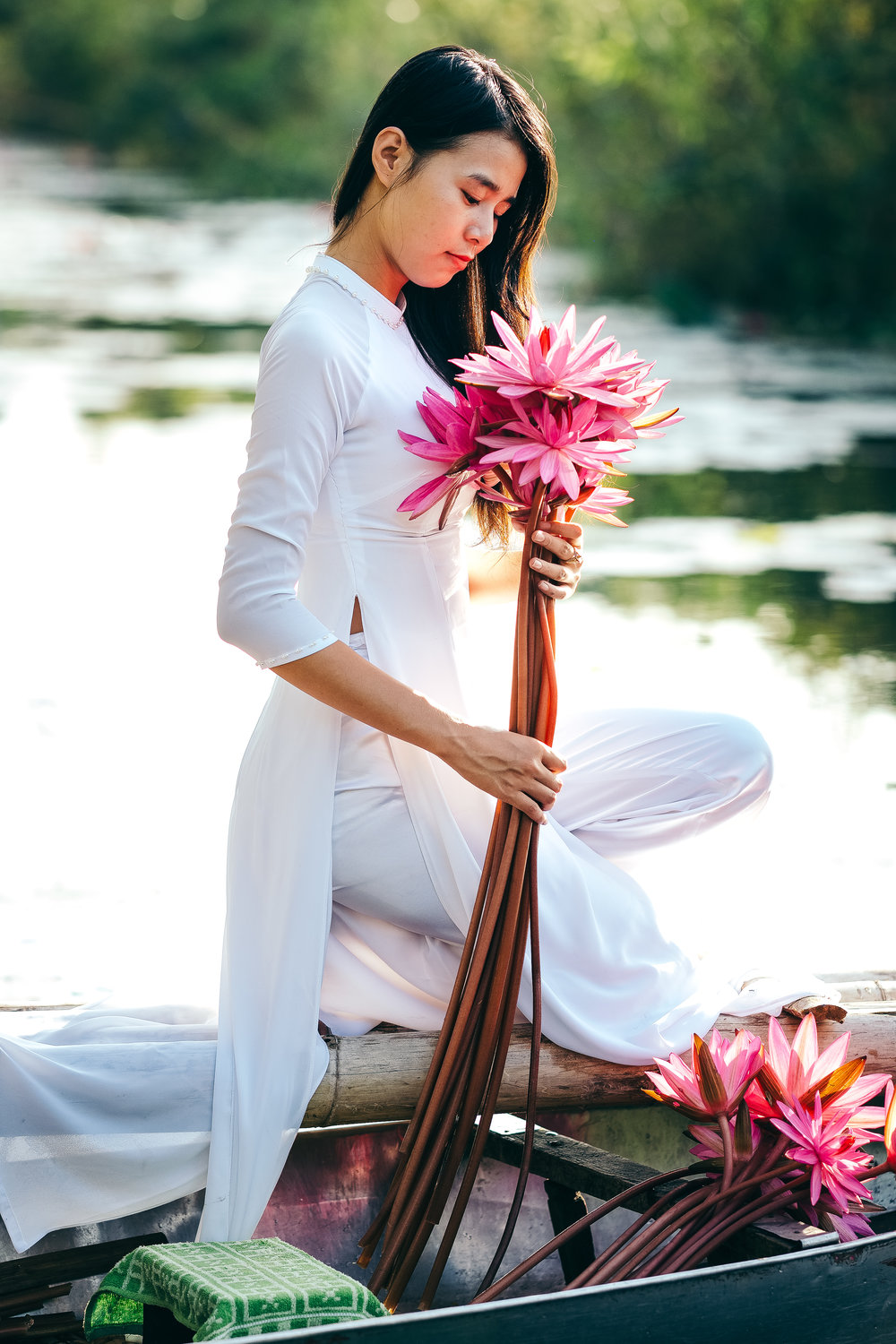 Vietnamese girl with red lotus in hands