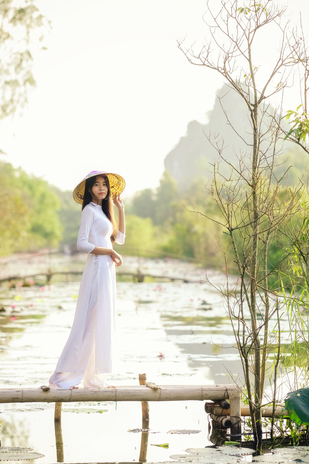 Vienamese girl in white ao dai dress standing on a wooden bridge