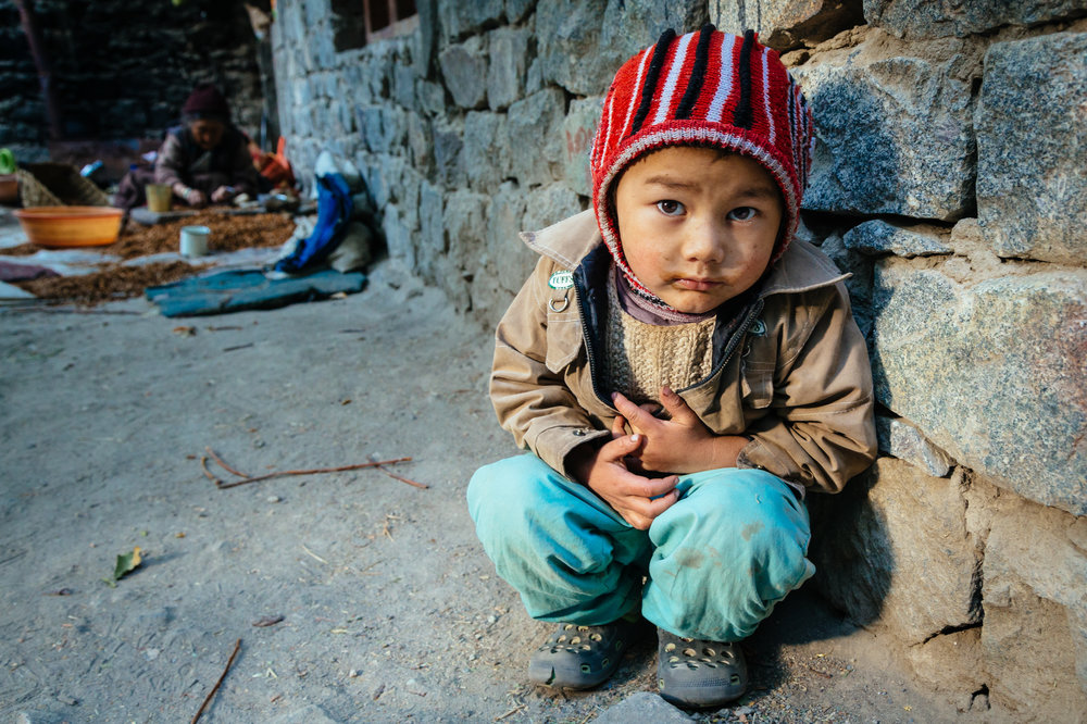 A curious child at his traditional house in a rural village in L