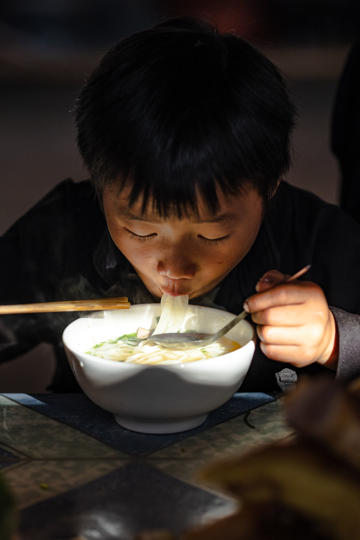 A boy enjoying his pho noodles in Dong van market in Vietnam.
