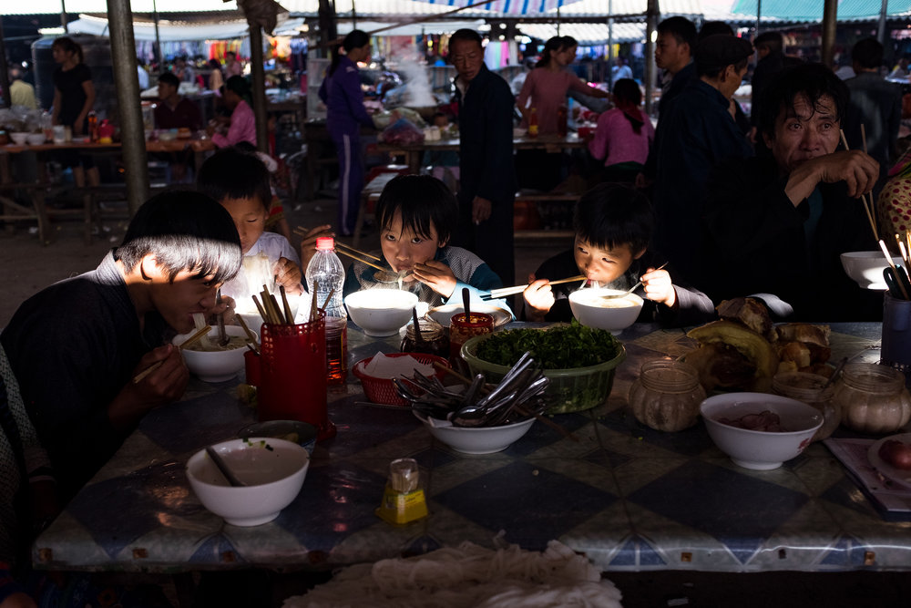 Group of young boys having pho noodles in Dong van market.