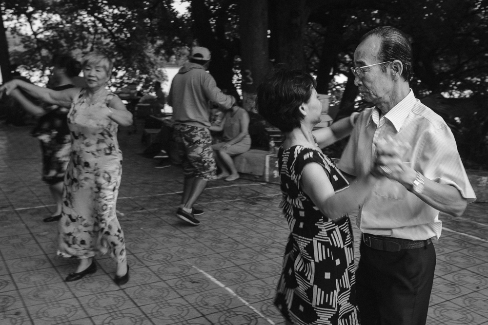 old couple dancing near Hoan kiem lake in Hanoi