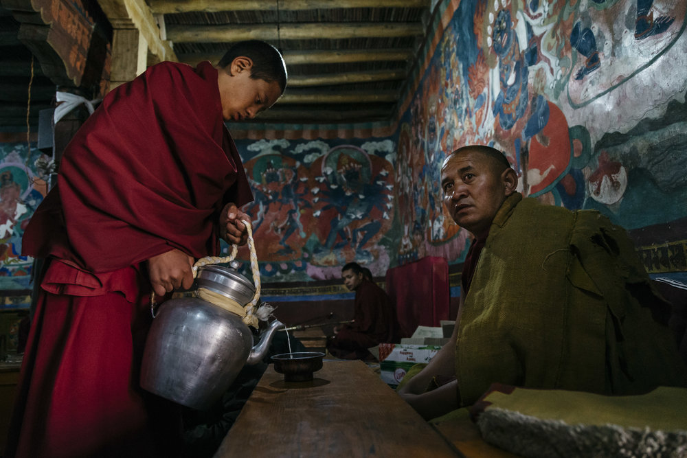A young Buddhist monk puring the morning breakfast into the bowl