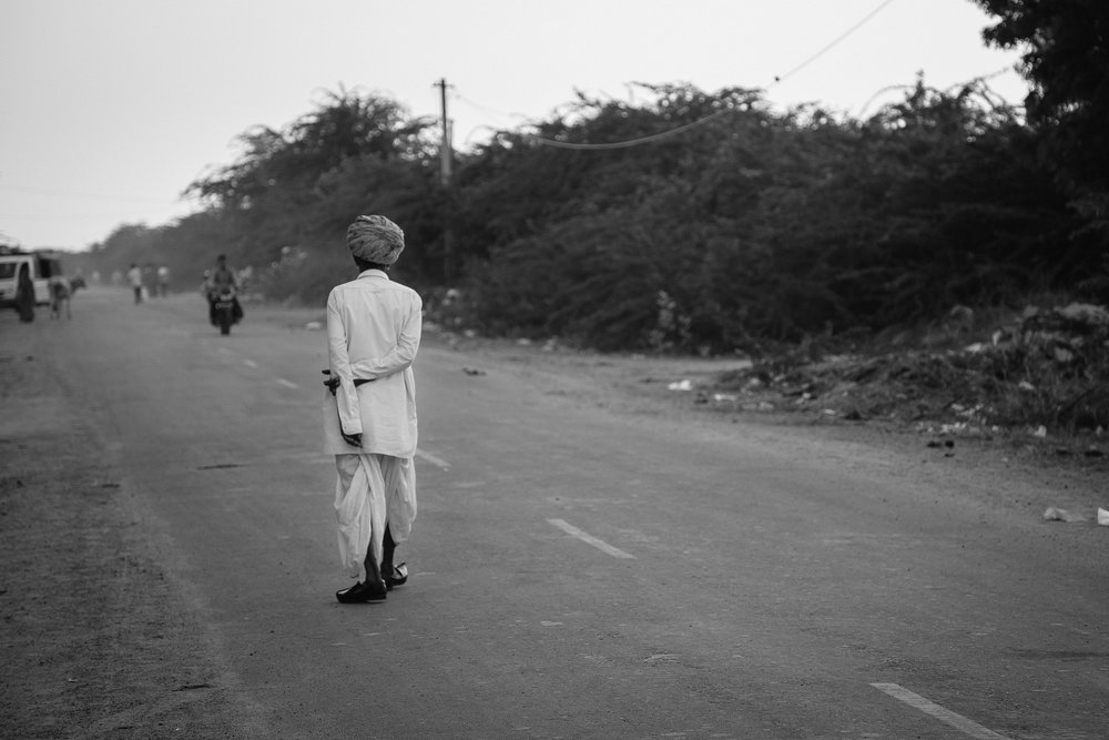 An old villager enjoying his evening walk on the tar road in Jod