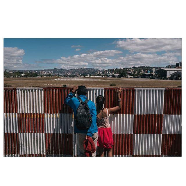 A man and his daughter stand outside the landing pit of the Carlota Military Airbase during a protest demanding the entrance of humanitarian aid in Caracas, Venezuela. / Un hombre y su hija observan la pista de aterrizaje de la base militar Carlota durante una protesta exigiendo la entrada de la ayuda humanitaria en Caracas, Venezuela.  ___________ #venezuela #caracas #photojournalism #photo #news