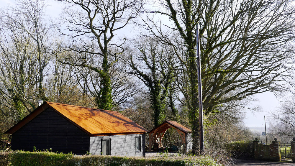 Charred timber, cor-ten roof, woodland structures
