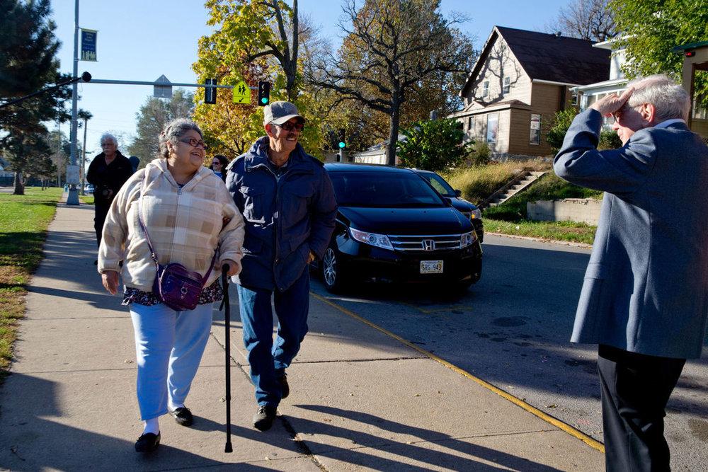 Foto de Amelia y Pedro Cruz caminando hacia su lugar de votación en noviembre del 2016 con Warren Buffet por  Sarah Hoffman/The World-Herald