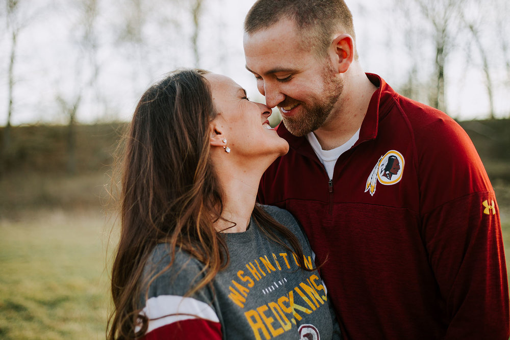 Shutter Up Studios | Wedding photographer in Crawfordsville Indiana | Golden hour engagement session kiss with Redskins shirts