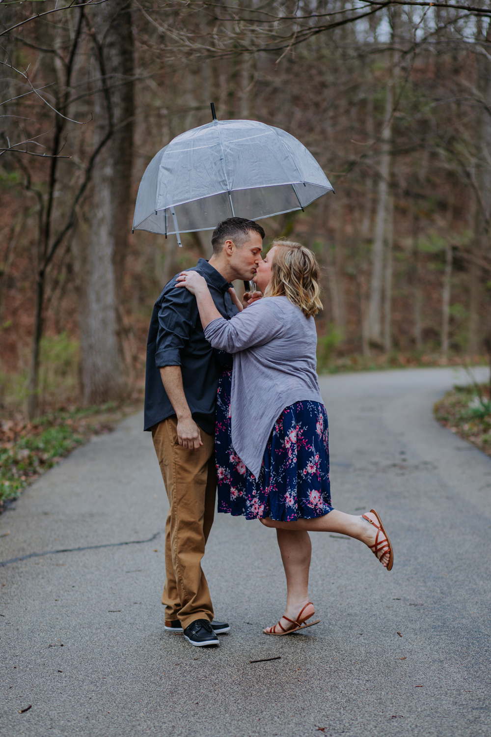 Shutter Up Studios   Engagement photographer in West Lafayette, Indiana   Rainy day couple kiss with clear umbrella at Happy Hollow Park
