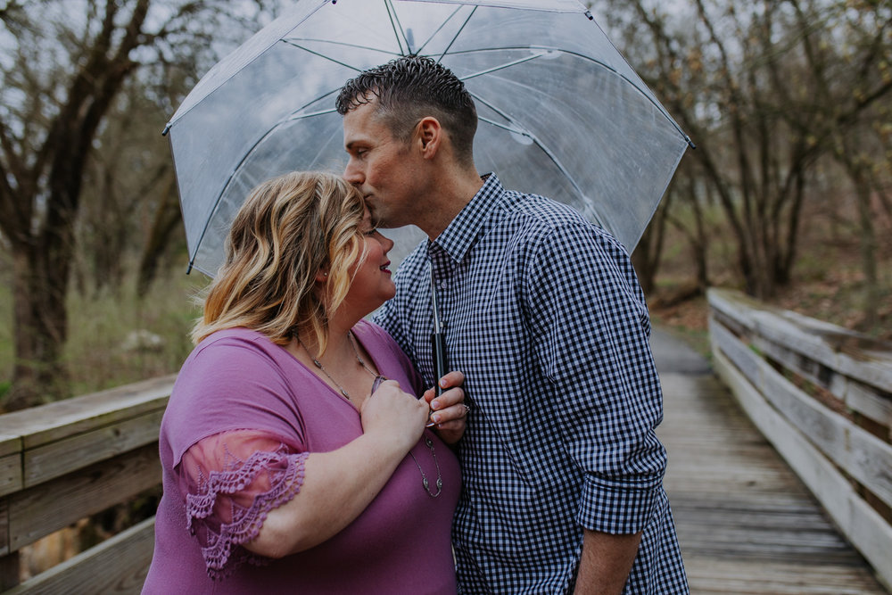 Shutter Up Studios   Engagement photographer in West Lafayette, Indiana   Rain couple forehead kiss with clear umbrella at Happy Hollow Park