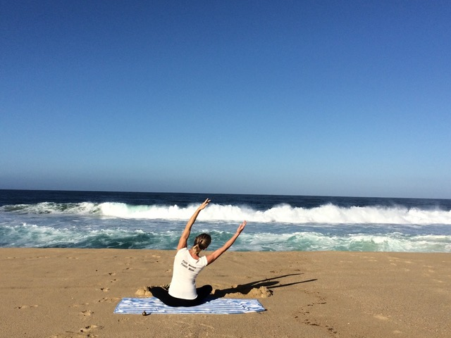 Kathleen Conklin doing yoga on the beach