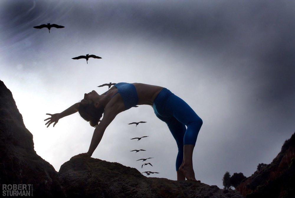 Robert Sturman photograph of a yoga pose with birds passing overhead
