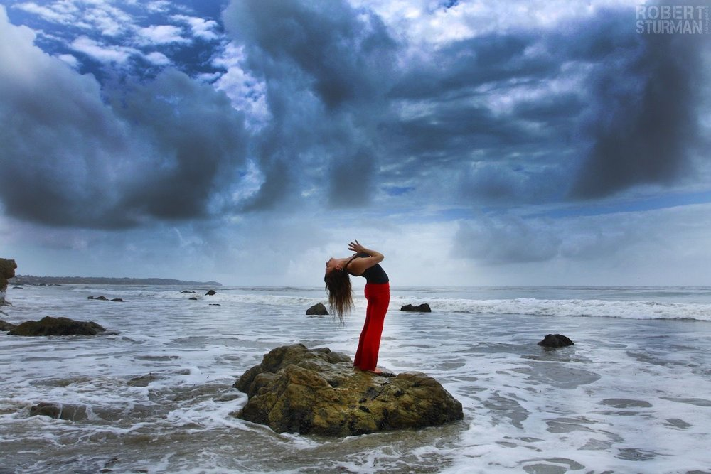 Robert Sturman photography of a yoga pose on a rock near the ocean